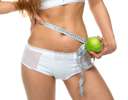 Young sport woman body measuring waist with tape measure