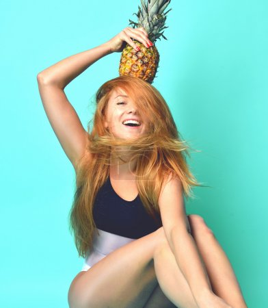 Young happy beautiful sexy woman posing laughing with pine apple
