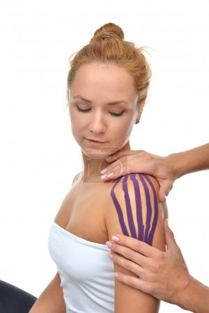 Doctor hands applying special physio tape on woman shoulder