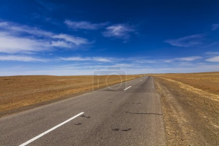 Lonely road in the desert under a blue sky.