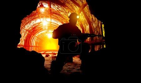 Photo pour Silhouettes du travailleur dans la mine . - image libre de droit