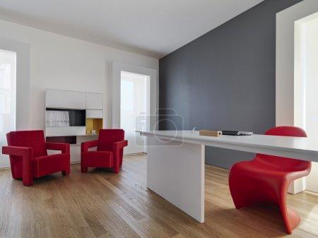 Photo pour Deux fauteuils rouges et un bureau blanc dans le salon moderne avec parquet - image libre de droit
