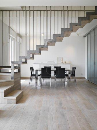Photo pour Vue intérieure d'une salle à manger moderne avec table à manger et escalier en fer le sol est en bois - image libre de droit