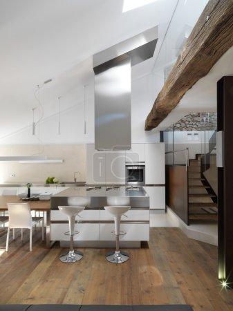 Photo pour Vue de l'île cuisine moderne avec plancher de bois près de l'escalier dans le penthouse - image libre de droit