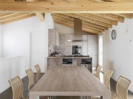Photo pour Table à manger moderne en bois donnant sur la cuisine avec plafond en bois - image libre de droit
