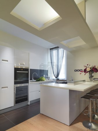 Photo pour Avant-plan d'une cuisine moderne avec îlot et plancher de bois - image libre de droit