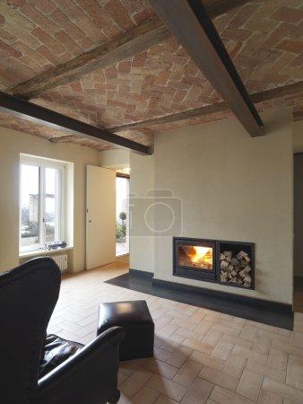 Photo pour Fauteuil en cuir noir devant la cheminée dans un salon pour une maison rustique vacante avec sol en terre cuite - image libre de droit
