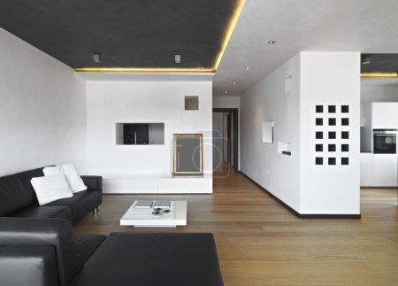 Photo pour Au premier plan d'un salon avec canapé leathee, sol bois, donnant sur la cuisine - image libre de droit