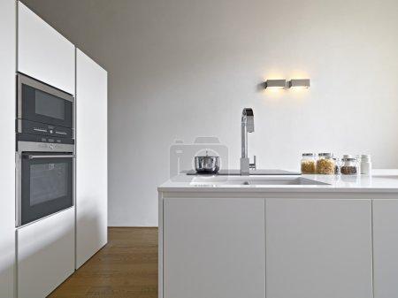 Photo pour Vue intérieure d'une cuisine moderne avec îlot de cuisine, évier et four le sol est en bois - image libre de droit