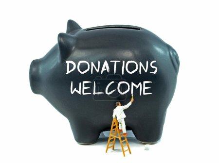 Photo pour Donations Welcome message painted on a piggy bank - image libre de droit
