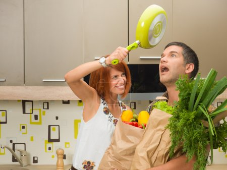 Photo for Close-up of young woman hitting  surprised shocked man on head with frying pan, both standing in kitchen - Royalty Free Image