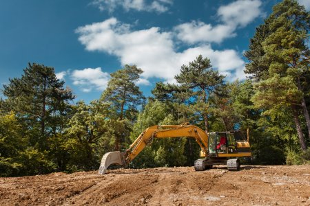 Photo for Side view of excavator on new construction site with trees and blue sky in background - Royalty Free Image