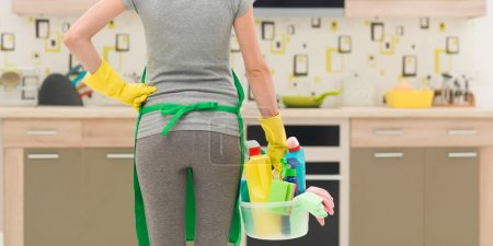Photo for Back view of cleaning lady standing in kitchen holding bucket with cleaning products - Royalty Free Image