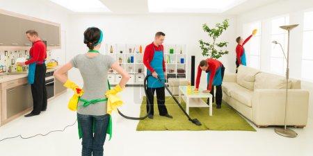 Photo pour Homme nettoie la maison à des endroits différents en même temps tandis que la femme superviser les progrès - image libre de droit