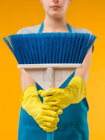 Photo for Close-up of cleaning woman holding blue broom in front of her, on yellow background - Royalty Free Image
