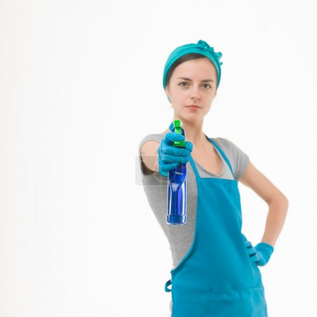 Photo for Portrait of cleaning woman aiming spray bottle in front of her, on white background - Royalty Free Image