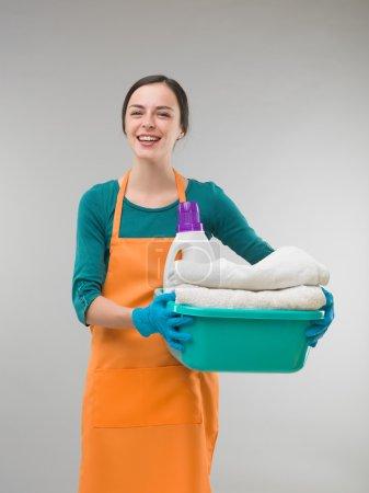 Photo pour Femme de ménage s'amuser tout en tenant des serviettes propres - image libre de droit