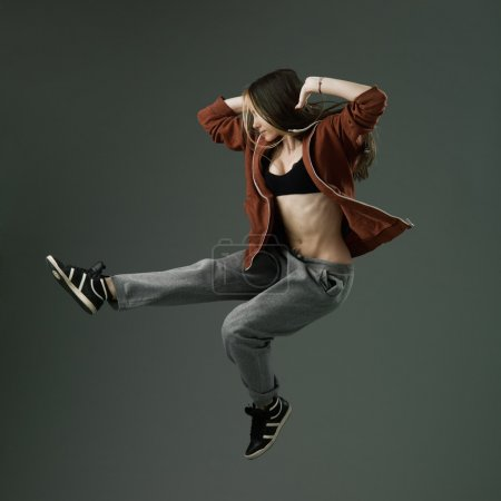 Photo for Happy modern style dancer jumping against grey studio background - Royalty Free Image