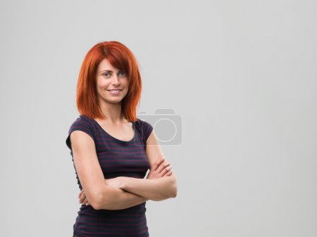 Photo for Portrait of young woman standing with crossed arms and smiling, against grey background - Royalty Free Image