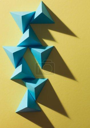 Foto de Construcción abstracta hecha de pirámides de papel, con sombras duras, sobre fondo amarillo - Imagen libre de derechos