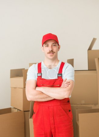 Photo for Young confident delivery man standing, holding hands crossed against his chest, with cardboard boxes in background - Royalty Free Image
