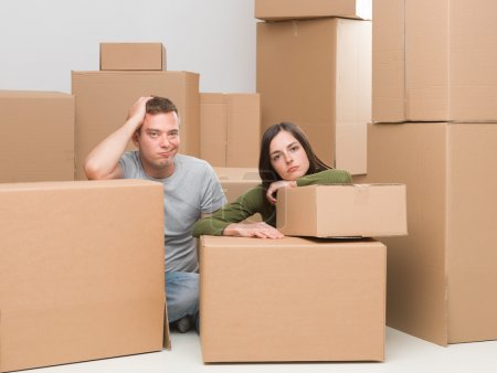 Photo for Couple sitting around cardboard moving boxes, sad about leaving their home - Royalty Free Image