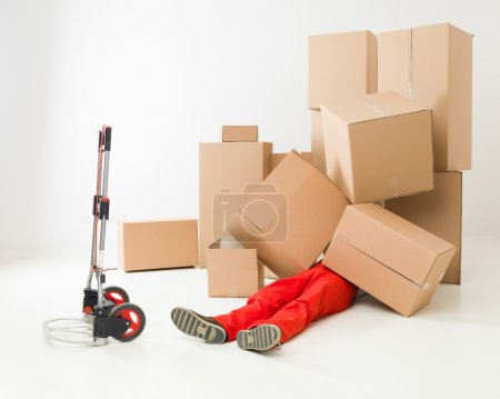 Photo for Delivery man laying on floor covered in cardboard boxes - Royalty Free Image
