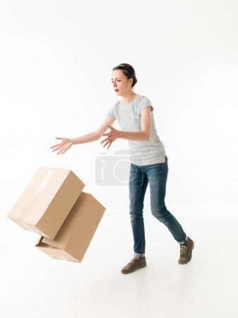 Photo for Clumsy young woman dropping moving boxes and tripping. on white background - Royalty Free Image