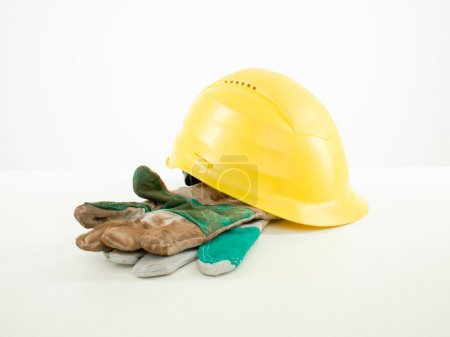 Photo for Yellow hardhat and dirty protective gloves, on white background - Royalty Free Image