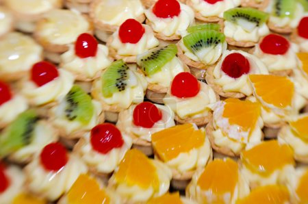 Photo for Close-up of small fruit tarts arranged in rows depending on the fruit, pineapple, kiwi, cherry and orange - Royalty Free Image