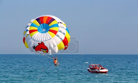 Parasailing in a blue sky.