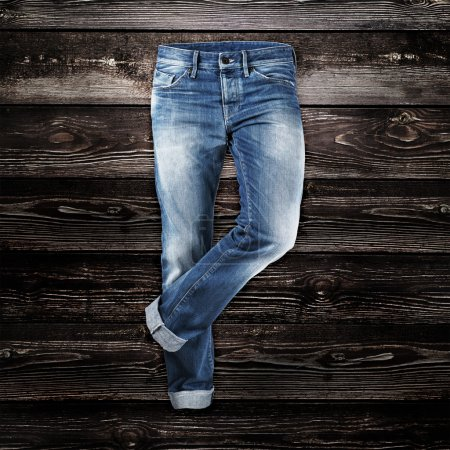 Photo for Jeans trouser over dark wood planks background - Royalty Free Image