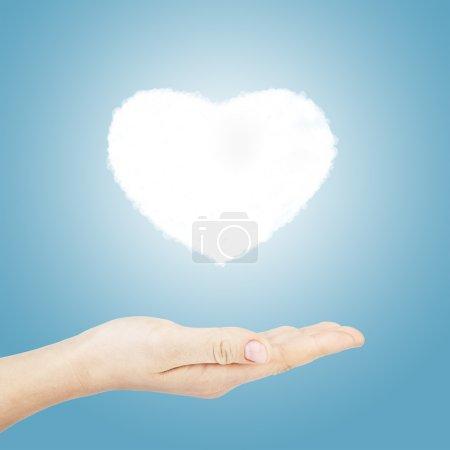 Photo pour Main tenir coeur forme nuage sur fond bleu - image libre de droit