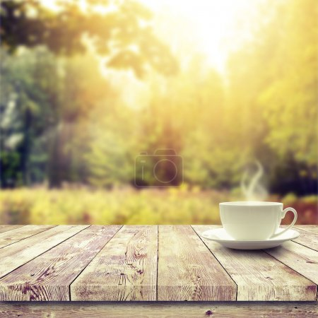 Photo for Cup with hot drink on wood table over forest  background - Royalty Free Image