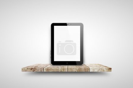 Tablet pc on wooden shelf