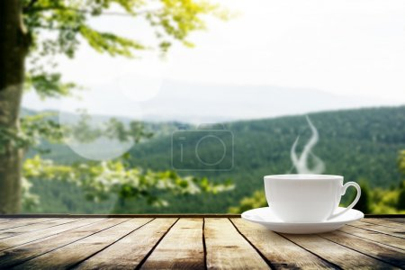 Cup with tea over mountains landscape