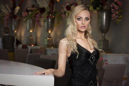 blond girl in cafe in black dress