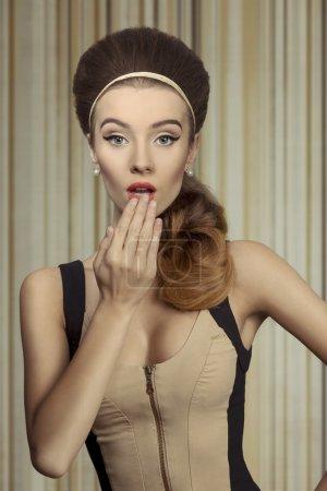 Foto de Joven, chica retro beautifil ajustado vestido crema y negro. tiene un gran estilista de grandes ojos azules, marrones y lleva perlas en las orejas. Ella es un poco sorprendida. - Imagen libre de derechos