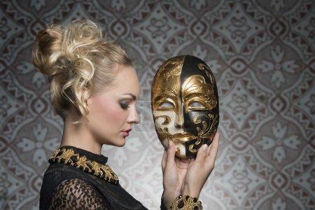 Photo pour Femme blonde sensuelle avec robe de carnaval gothique antique et bijoux baroques posant avec masque théâtral dans les mains - image libre de droit