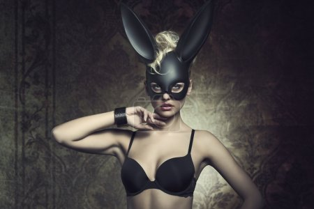 Photo for Fashion Easter creative portrait of mysterious woman with blonde curly hair-style and lack bra posing with cute dark bunny mask. Fetish atmosphere - Royalty Free Image