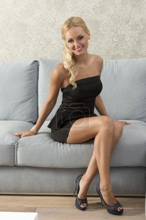 Photo pour Souriant belle fille, assis sur le canapé dans son salon, dans une situation élégante  . - image libre de droit