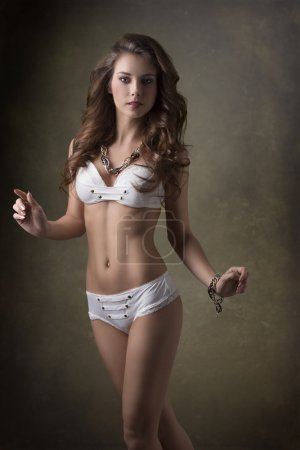 Photo for Sexy brunette girl with long natural wavy hair, white bikini and  trendy jewellery posing in fashion summer portrait - Royalty Free Image
