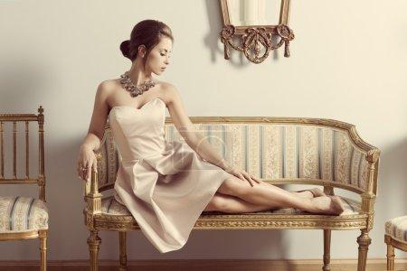 Photo pour Portrait intérieur de brune élégante fille couchée sur un canapé rétro dans une chambre aristocratique. Porter une robe rose, des bijoux précieux et une coiffure classique. Atmosphère de luxe - image libre de droit