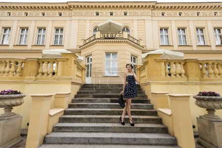 Rich girl in blue near a big palace