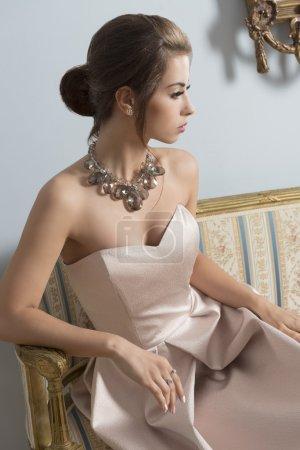 Photo pour Portrait d'intérieur d'une fille brune aristocratique assise sur un canapé vintage avec une élégante robe rose, un collier brillant et une coiffure classique. Fille de luxe dans la chambre antique - image libre de droit