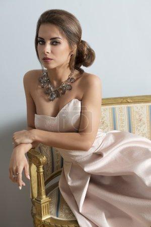 Photo pour Élégante fille brune avec un style riche posant avec robe rose élégante et collier précieux sur vieux canapé en portrait d'intérieur - image libre de droit