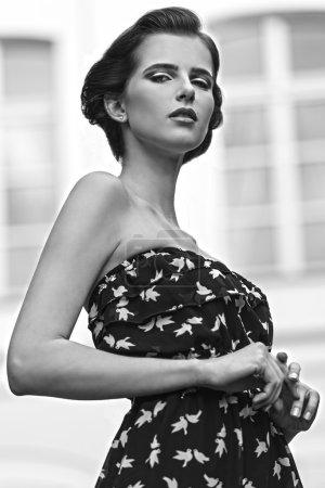 Photo pour Noir et blanc, charmante femme brune posant en extérieur portrait de mode avec robe sexy d'été et coiffure élégante. Poser avec un vieux bâtiment sur le fond et regarder à la caméra - image libre de droit