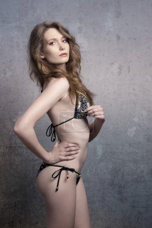 Photo pour Provocante femme dans une pose sexy avec les cheveux longs ondulés et maillot de bain élégant cherche à huis clos - image libre de droit