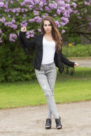 Photo pour Charmante jeune femme posant en plein air dans le parc vert avec de longs cheveux naturels, maquillage rock, veste en cuir mignon, jeans déchiré et chaussures sexy. Tenue urbaine tendance - image libre de droit