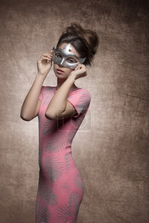Photo for Very sexy young woman with brunette hair-style, sexy pink dress and silver mask on her face - Royalty Free Image